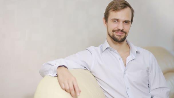Portrét chlap na gauči při pohledu na fotoaparát. Mladý muž s košili v pohodlí domova