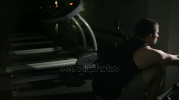Svalnatý muž sportovní trénink na simulátoru trénink v tělocvičně crossfit