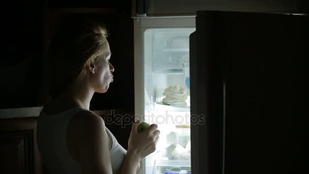 Žena otevírá lednici v noci. bulimie, sendvič, pečivo