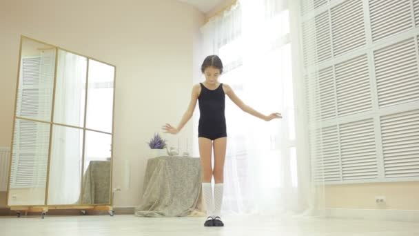 little girl in a bathing suit gym rehearsing at home in front of a mirror