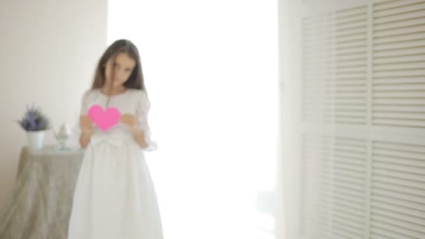 Happy usmívající se dívka ukazuje červené srdce. Valentinky den