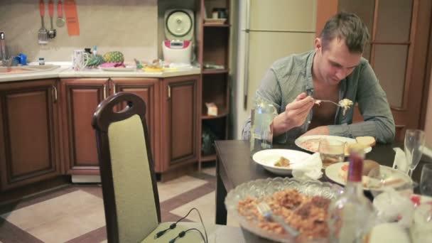 junger Mann mit einem Kater am Tisch in der Küche. After-party