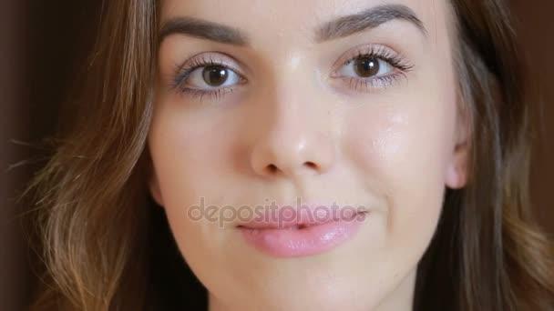 krásná mladá bruneta dívka při pohledu na fotoaparát s úsměvem