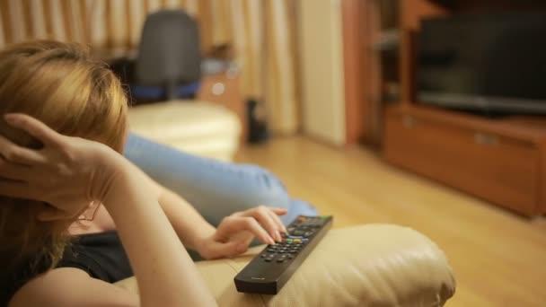 Krásná žena, sledování televize, sedí na gauči doma, změny kanálů