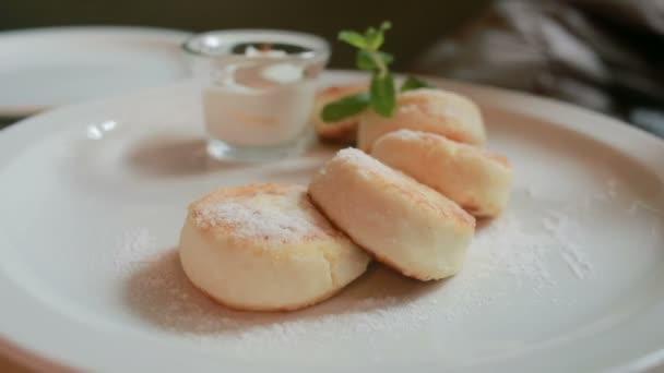 dívka v kavárně jíst sýr lívance s kysanou smetanou vidlička a nůž