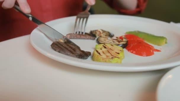 ženské ruce zblízka pokrájenou zeleninu a grilované maso na talíři