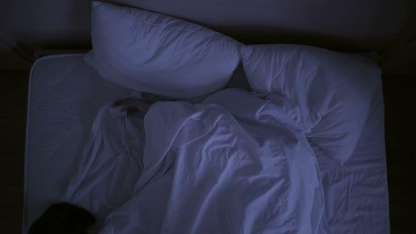 Koncept nespavost. muž v posteli v noci nemůže spát