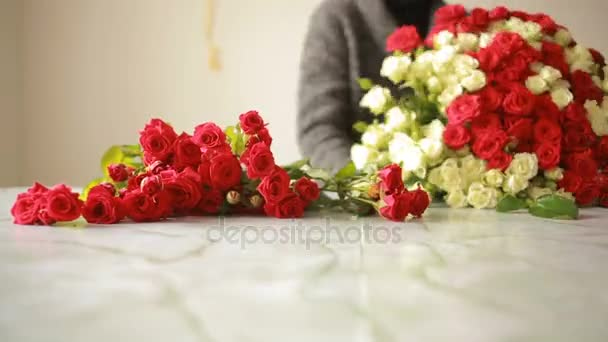 bright colorful bouquet of red and white roses, florist woman gathers a bouquet