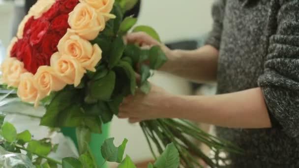 fényes színes csokor őszibarack és piros rózsák, virágüzlet nő összegyűjti egy csokor