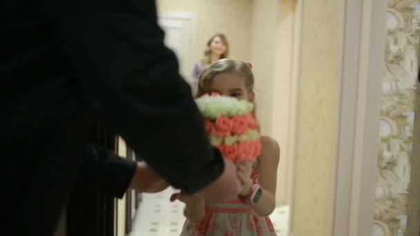 kleines Mädchen mit einem zarten Strauß rosa und weißer Rosen