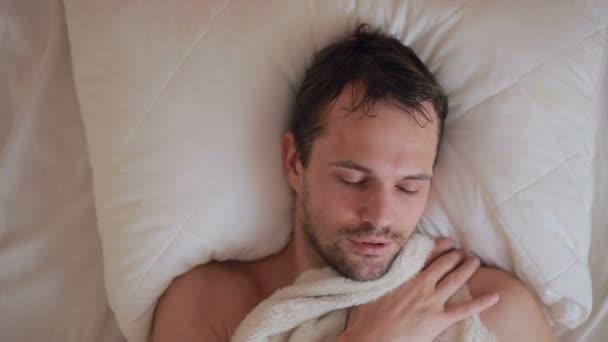 ein Mann mit einem Fieber liegt im Bett zu Hause