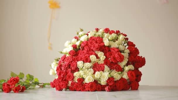 světlé barevné kytice z červených a bílých růží, květinářství žena shromažďuje kytice