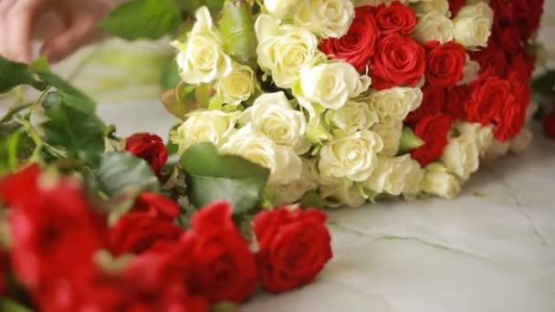 fényes színes csokor vörös és a fehér rózsák, virágüzlet nő összegyűjti egy csokor