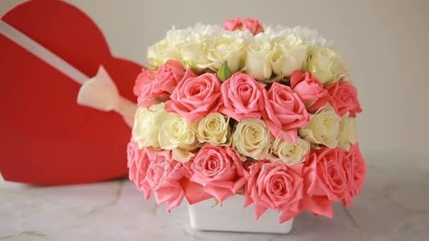 zarter Strauß rosa und weißer Rosen. Schachtel mit einem Geschenk in Herzform