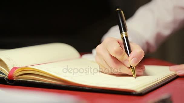 Eine weibliche Hand schreibt einen Stift auf Papier.