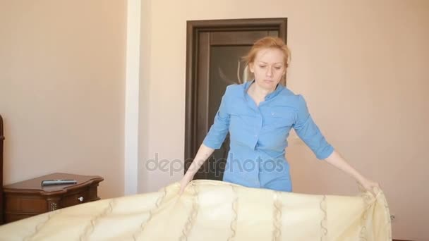 Služebná dělá úklid v ložnici