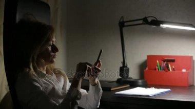 žena sedí v kanceláři na stůl a psal zprávy na smartphone