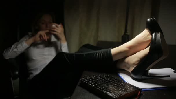 žena sedí v kanceláři na stůl a psal zprávy na smartphone.