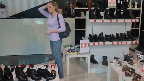 blond žena vybere obuv v butiku boty