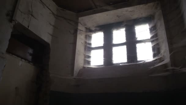 The terrible old eerie windows of the old house are all in a cobweb. inside view