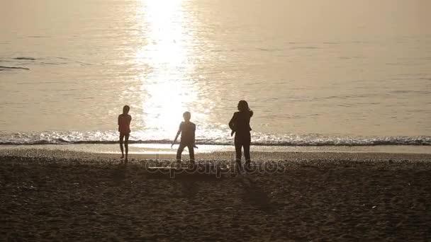 Sagome di persone in piedi al tramonto in riva al mare. donna e bambini