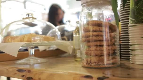 Croissanty a ovesné vločky cookies ve skleněné nádobce na předváděčce café