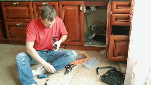 Zdravotechnické oprava úniku vody. muž upevňovací kohoutek v kuchyni