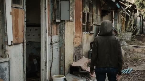 A teenager wanders around the Old abandoned house, a view from the street.