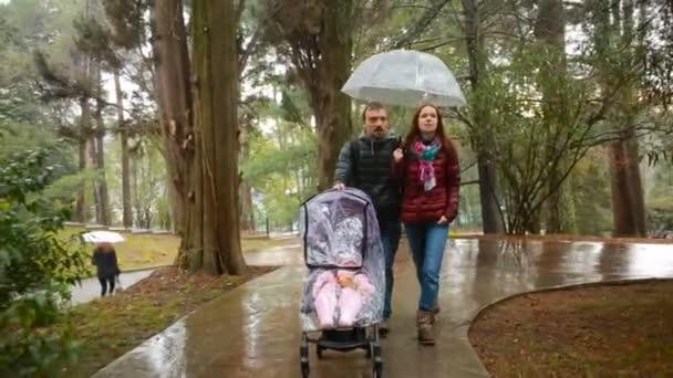 Máma a táta, hrát si s jejich dítě sedící v kočárku: procházka v parku