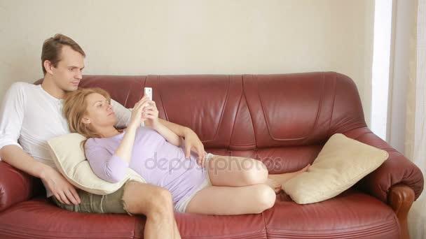 Mladý pár odpočinku na gauči v obývacím pokoji, jemně objímá a mluví