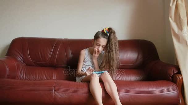 Malá holčička dělá selfie na smartphone doma na gauči