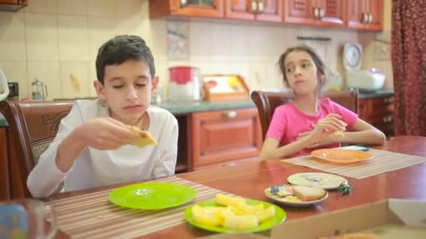 Junge und Mädchen, Zwillinge essen Pizza und Obst, während sie in der Küche am Tisch mit dem Handy spielen