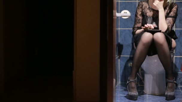 Woman sitting in public toilet. Using a smartphone, tablet