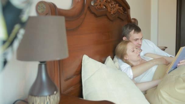 Donna e uomo delle coppie che si trovano sul letto nella camera da ...