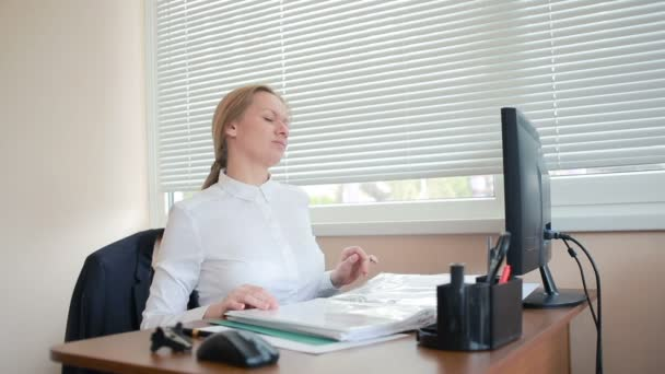 Woman manager tired of work doing physical exercises at the table in the office