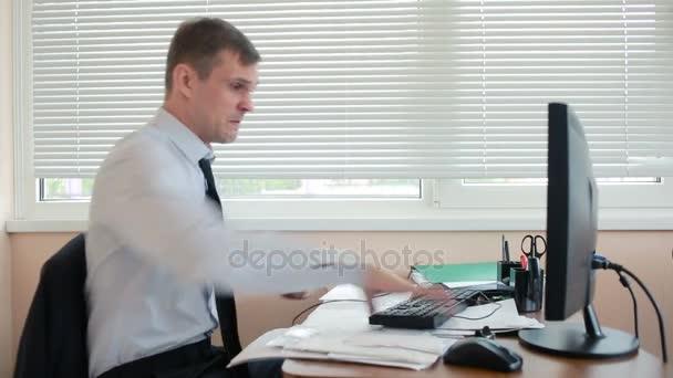 Geschäftsmann, Manager zerschmettert wütend Tastatur auf Schreibtisch, sitzt im Büro