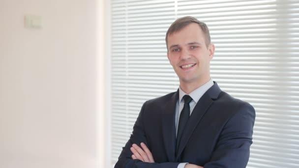 Mladý podnikatel stojící v kanceláři na pozadí rolety ukazovat gesto palce na fotoaparátu