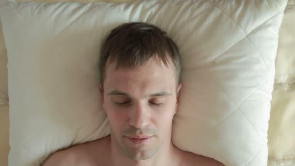 Egy ember alszik egy ágyban a nyugtalan alvás. A másnapos ébredés. Közelről. Nézd meg felülről