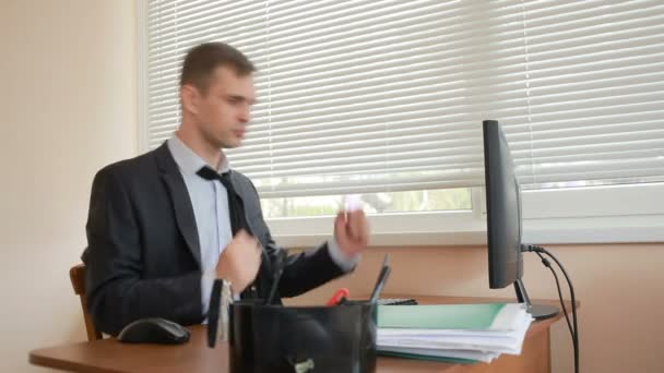 manager tired of work doing physical exercises at the table in the office