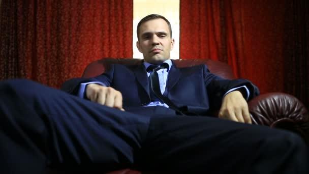 Brutális férfi bőr karosszékben ül, néz a kamerába, és gesztikuláló öltöny. Ujjal mutat a kamera, utánozva egy lövés