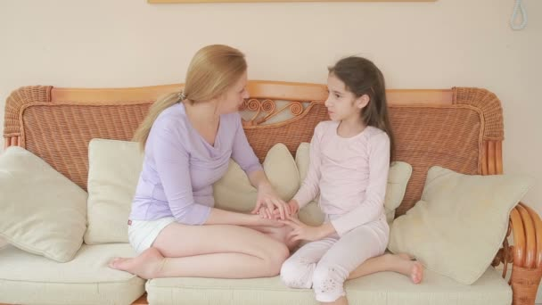 Máma a dcera mluví od srdce k srdci doma na proutěné sofa