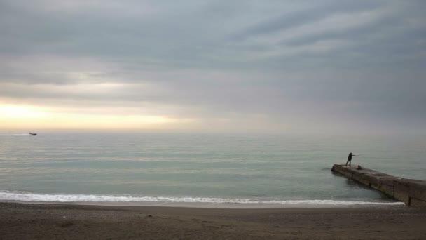 Siluety lidí, kteří stáli na molo při západu slunce u moře, časová prodleva