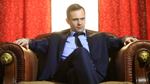 Brutal man in a suit sitting in a leather armchair, looking into the camera and gesticulating. Hands at the person touches a chin and a forehead, gestures of thinking, decision-making,