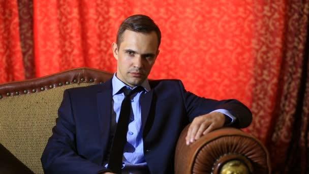 Brutální muž v obleku, sedí v koženém křesle, při pohledu do kamery a rukama. Ruce na osobu se dotýká, bradu a čelo, gesta myšlení, rozhodování
