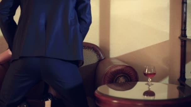 Muž v obleku je třecí pohyby, imitující pohlavní styk. Pár má sex na židli