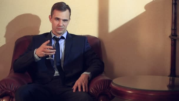 A brutal man in a suit sits in a leather chair with a glass of alcohol, looks at the camera