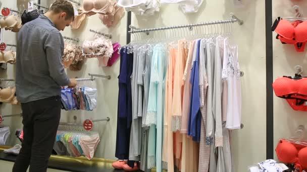 2f5ba42f6 Hombre elige bragas de una chica en una tienda de ropa interior para mujer–  metraje de stock