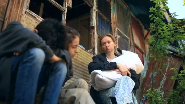 Refugee children and their mother with a child in the arms on the background of bombed houses. War, earthquake, fire