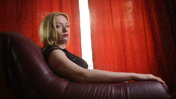 Fatální žena v černých šatech a červenou rtěnkou na rtech sedí v koženém křesle a arogantně vypadá na kameru, prstem ukazuje na kameru a vábí k sobě
