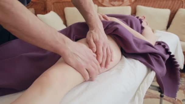 männlicher Masseur führt Fußmassage für Frauen, Hüften, Anti-Cellulite-Massage durch